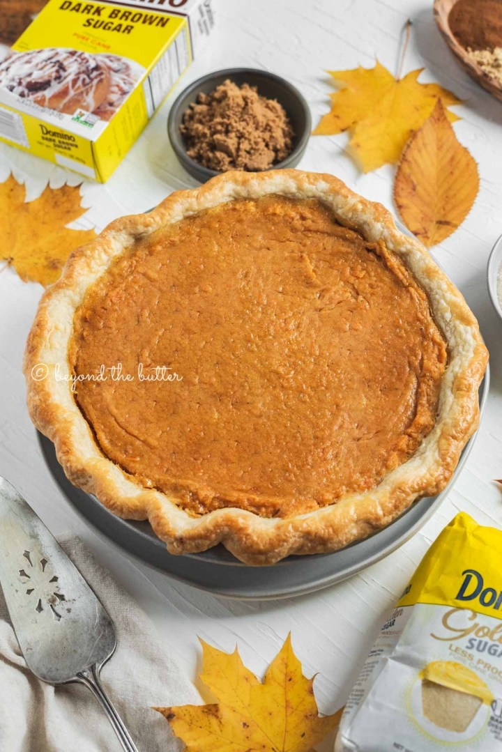 Angled image of brown sugar sweet potato pie without the marshmallow meringue topping with Domino® Sugar products around it | All Images © Beyond the Butter®