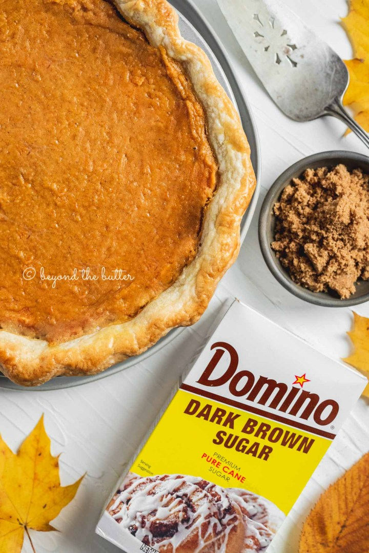 Overhead image of sweet potato pie with box of Domino® Dark Brown Sugar shown below it along with some colorful fall leaves | All Images © Beyond the Butter®