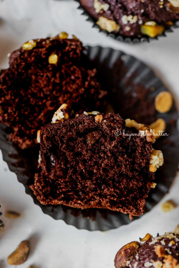 Dark chocolate pistachio cream cheese muffins with center muffin unwrapped and cut in half | All Images © Beyond the Butter™