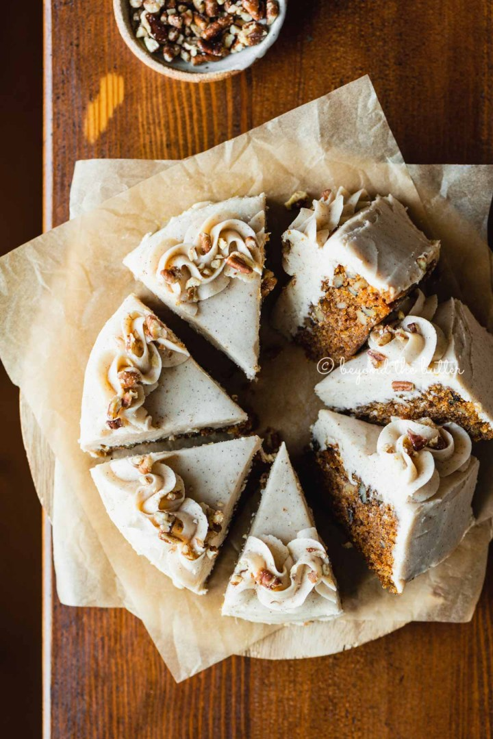 Overhead image of single layer carrot cake frosted on parchment paper and placed on a wood dining room table | All Images © Beyond the Butter®