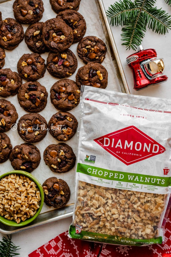 Large bag of Diamond Nuts chopped walnuts next to a parchment paper lined baking sheet filled with dark chocolate cranberry walnut cookies and tree ornament | All Images © Beyond the Butter®