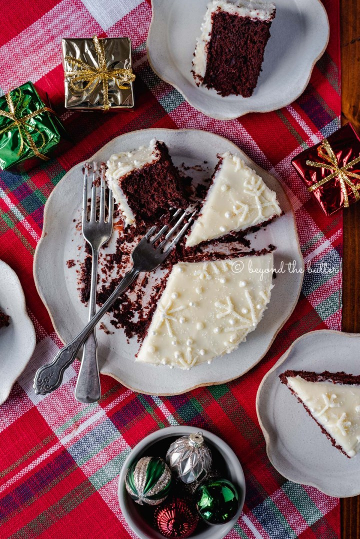 Half eaten and sliced red velvet cake with cream cheese frosting on a scalloped edge dessert plate with red plaid background | All Images © Beyond the Butter®
