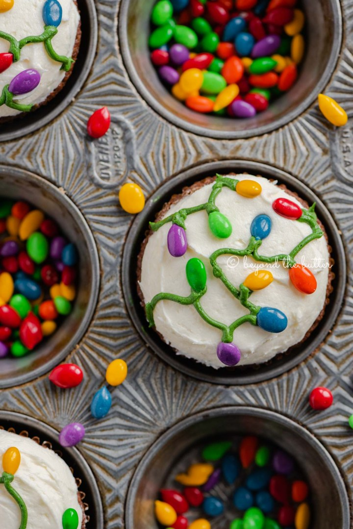 Cupcake tin with decorated small batch gingerbread cupcakes with marshmallow frosting and rainbow chocolate covered sunflower seeds   All Images © Beyond the Butter®