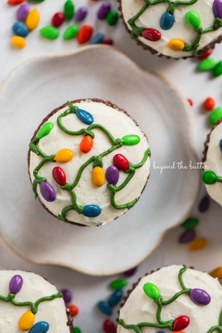 Small batch gingerbread cupcakes with one on a small dessert plate on a white, chocolate covered sunflower seed background   All Images © Beyond the Butter®