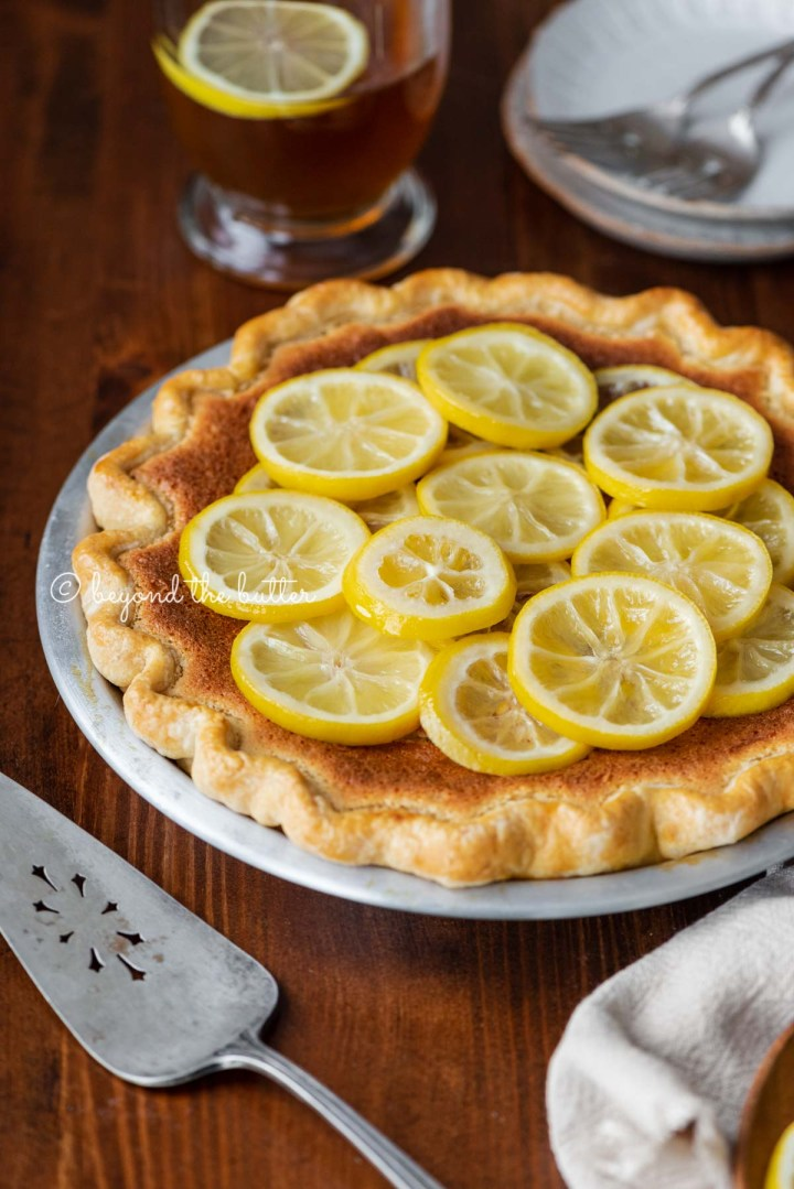 lemon sponge pie on a dark wood dining room table with hot lemon tea | All images © Beyond the Butter®