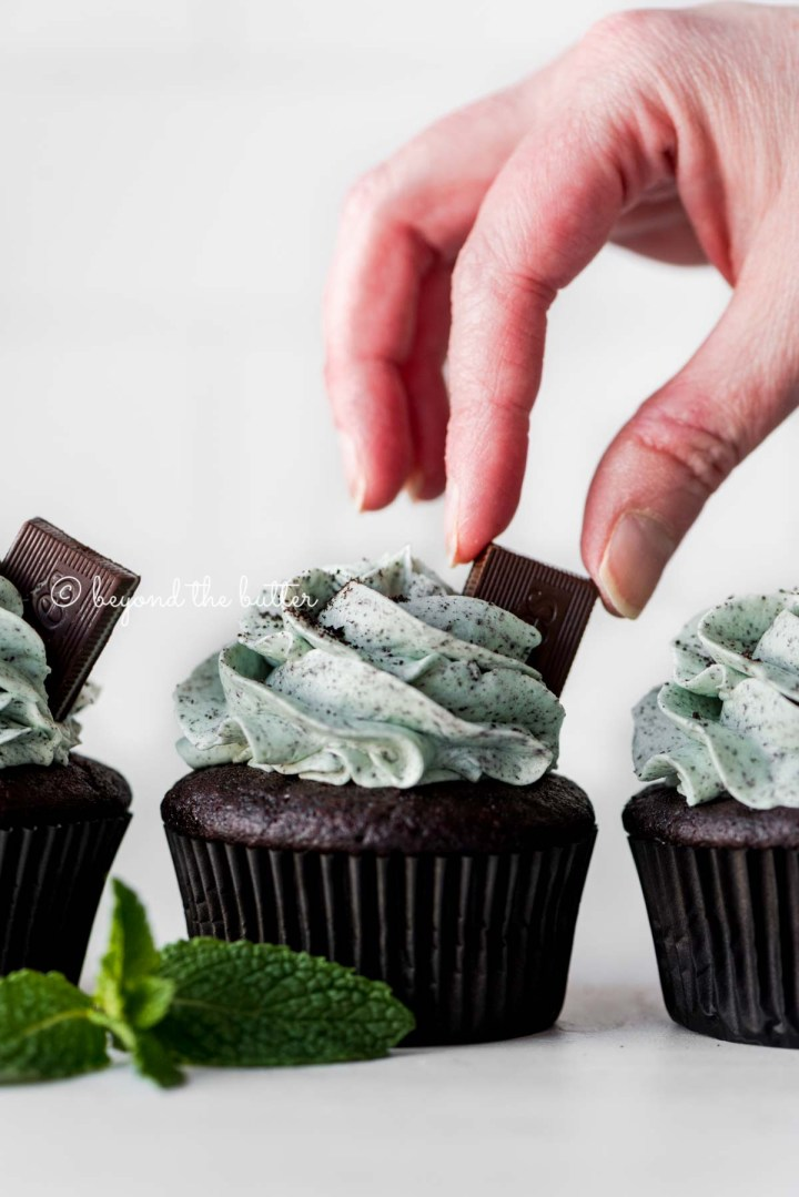 Placing an Andes mint on top of a mint chocolate cupcake for garnish | All Images © Beyond the Butter®