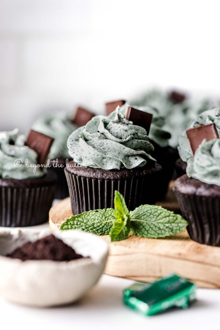 Mint chocolate cupcakes on a wood circular tray with mint leaves as decoration | All Images © Beyond the Butter®