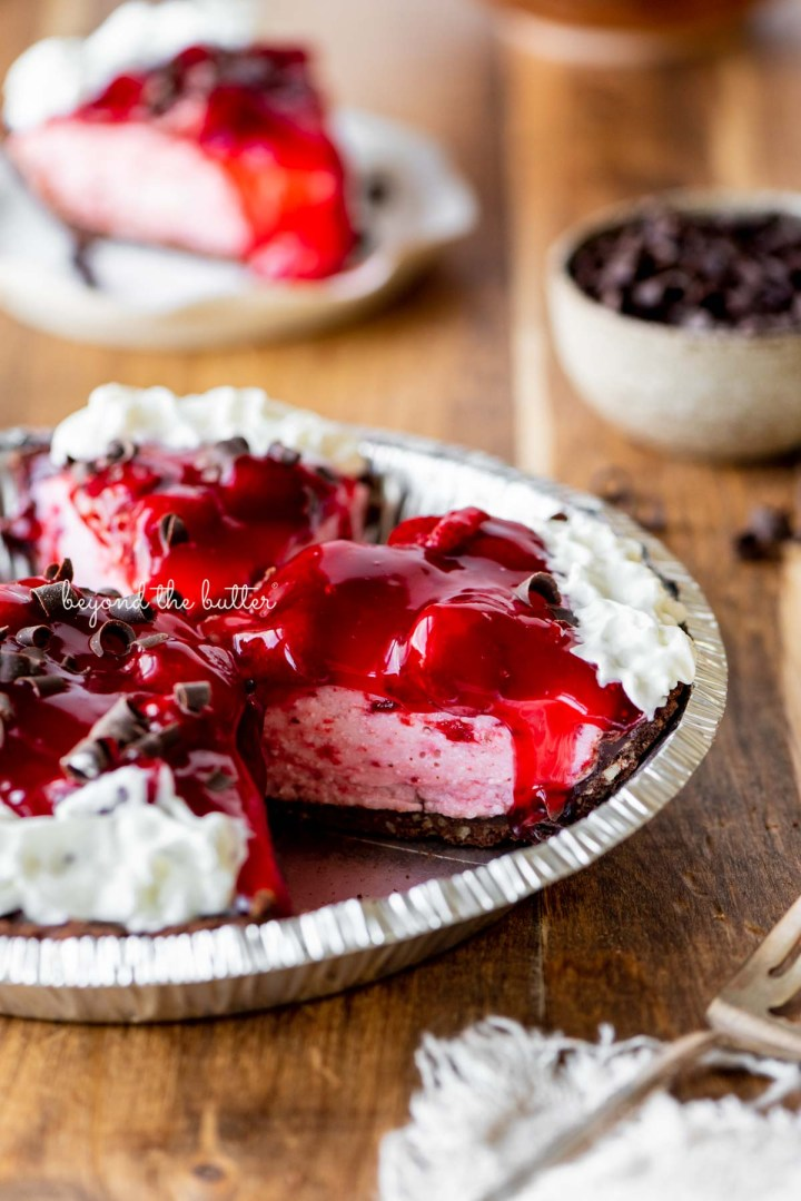 Sliced no bake strawberry chocolate cream pie on wood table with a fork and small bowl of chocolate curls nearby | All images © Beyond the Butter®