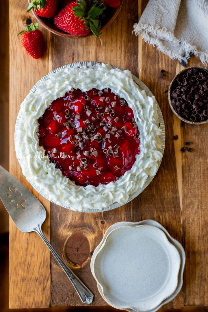 Decorated no bake strawberry chocolate pie with small bowl of chocolate curls and strawberries, dessert plates, and pie server on wood table | All images © Beyond the Butter®