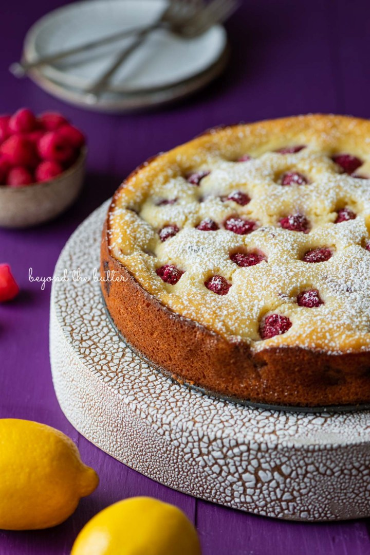 Lemon raspberry ricotta cake dusted with powdered sugar on crackled ceramic cake stand and purple wood background | © Beyond the Butter®