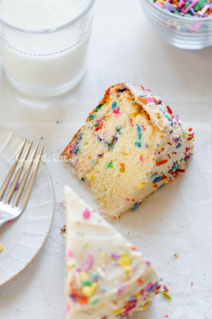 Slices of single layer funfetti cake on their side with a dessert plate, small fork, and glass of milk nearby from BeyondtheButter.com | All images © Beyond the Butter®