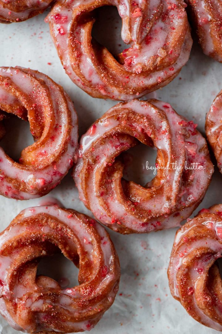 Strawberry glazed french crullers sprinkled with strawberry sugar on a parchment paper lined baking sheet | © Beyond the Butter®