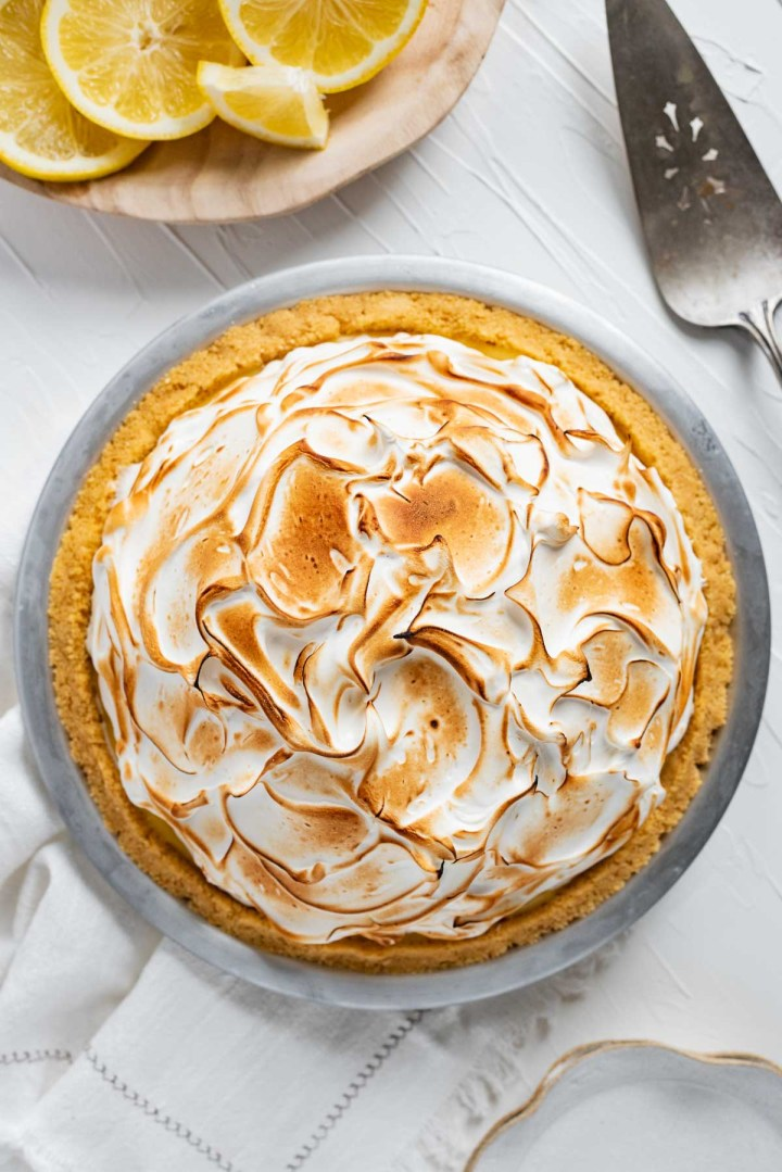 Lemon Merginue Ice Cream Pie with bowl of sliced and cut lemons and pie server above on white stucco background | © Beyond the Butter®