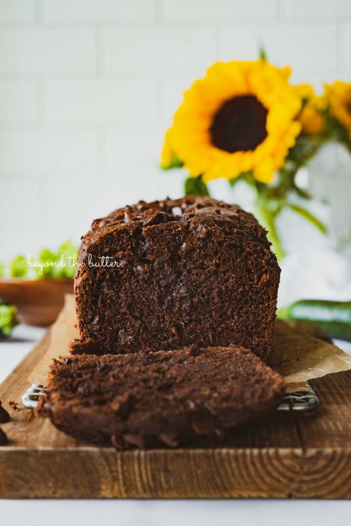 Sliced chocolate zucchini bread on a cutting board with white tile background and sunflowers | © Beyond the Butter®