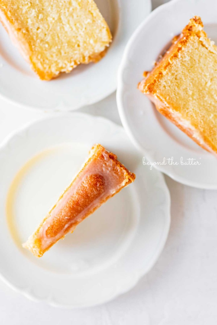 Slices of lemon cream cheese pound cake on small white dessert plates | © Beyond the Butter®