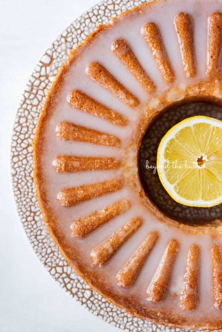 Glazed lemon cream cheese pound cake on a ceramic cake stand from Sweetheart Ceramics | © Beyond the Butter®