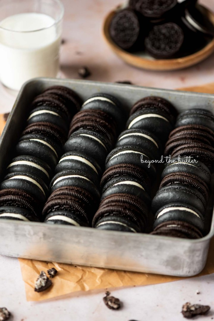 Oreo macarons and oreo cookies in a vintage baking tin on parchment paper with a glass of milk and bowl of oreo cookies in the background | © Beyond the Butter®