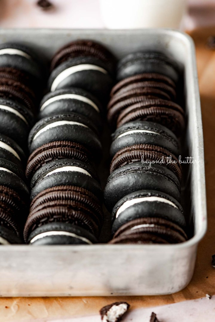 Oreo macarons and oreo cookies in a vintage baking tin on parchment paper | © Beyond the Butter®