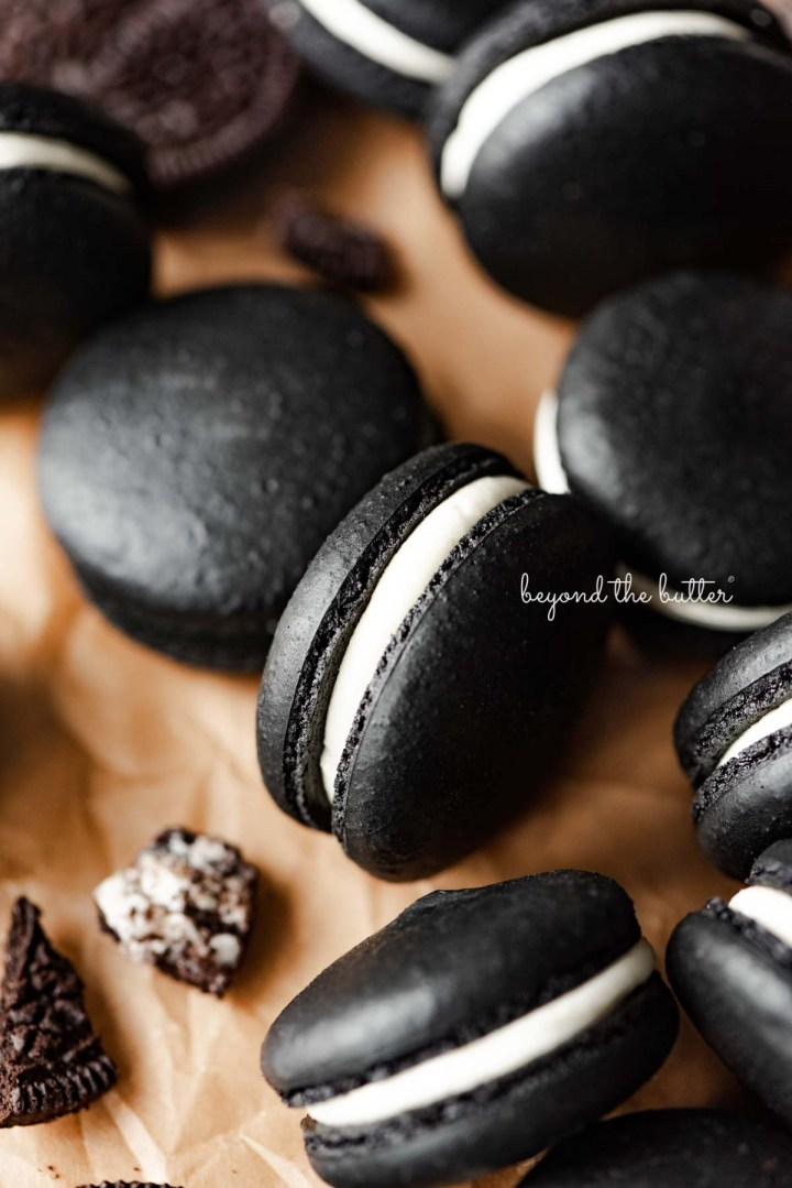 Oreo macarons on parchment paper with broken pieces of oreo cookies nearby | © Beyond the Butter®