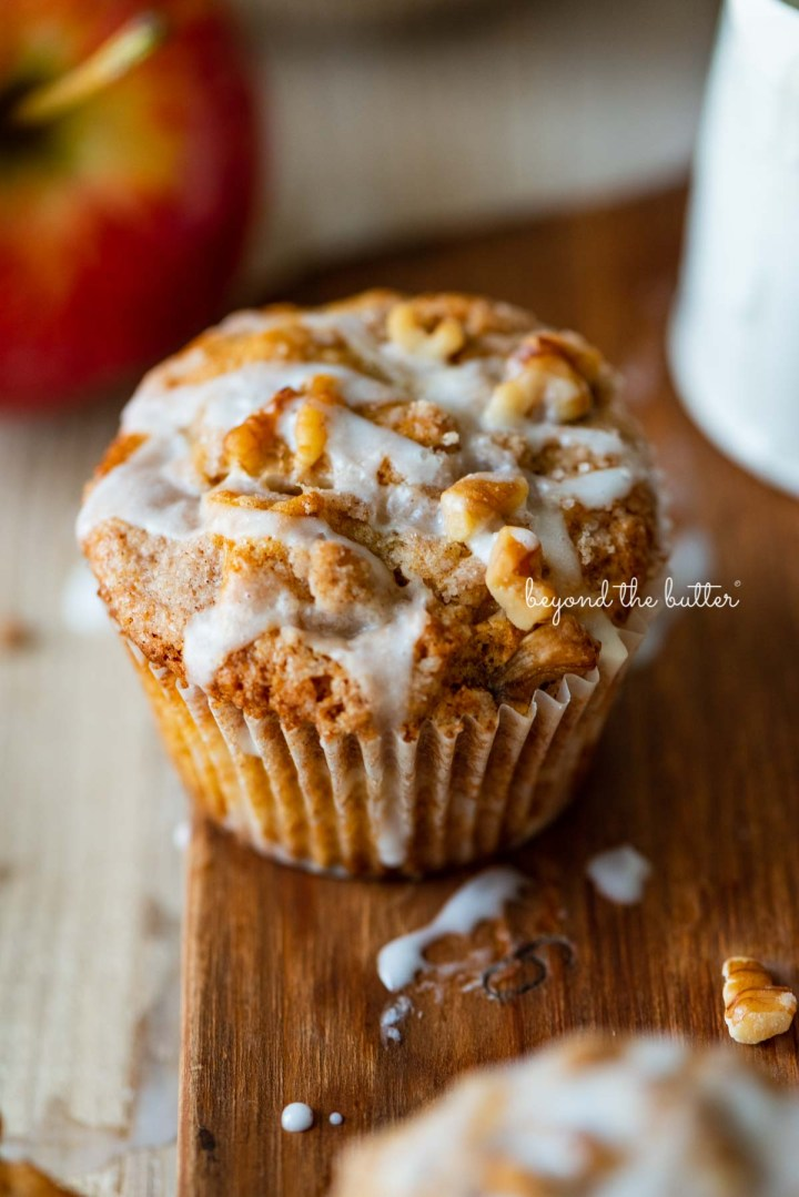 Apple cinnamon streusel muffin on a wood cutting board with slices of apples and vanilla glaze | © Beyond the Butter®