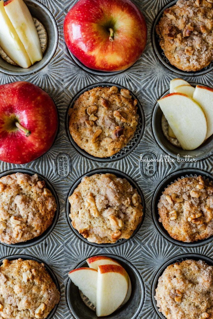 Vintage muffin tin with apple cinnamon streusel muffins and whole and sliced apples | © Beyond the Butter®
