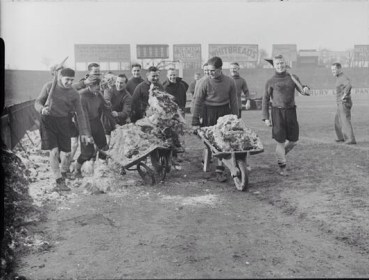 1939 - Fulham players help clear the snow at Craven Cottage before a cup tie against Bury