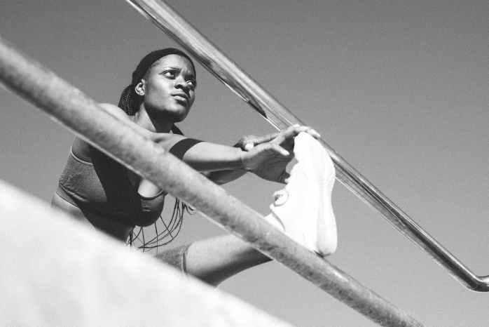 monochrome photo of woman leaning on metal railings