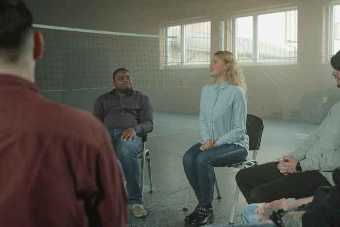 woman in blue long sleeve shirt sitting beside man in black jacket
