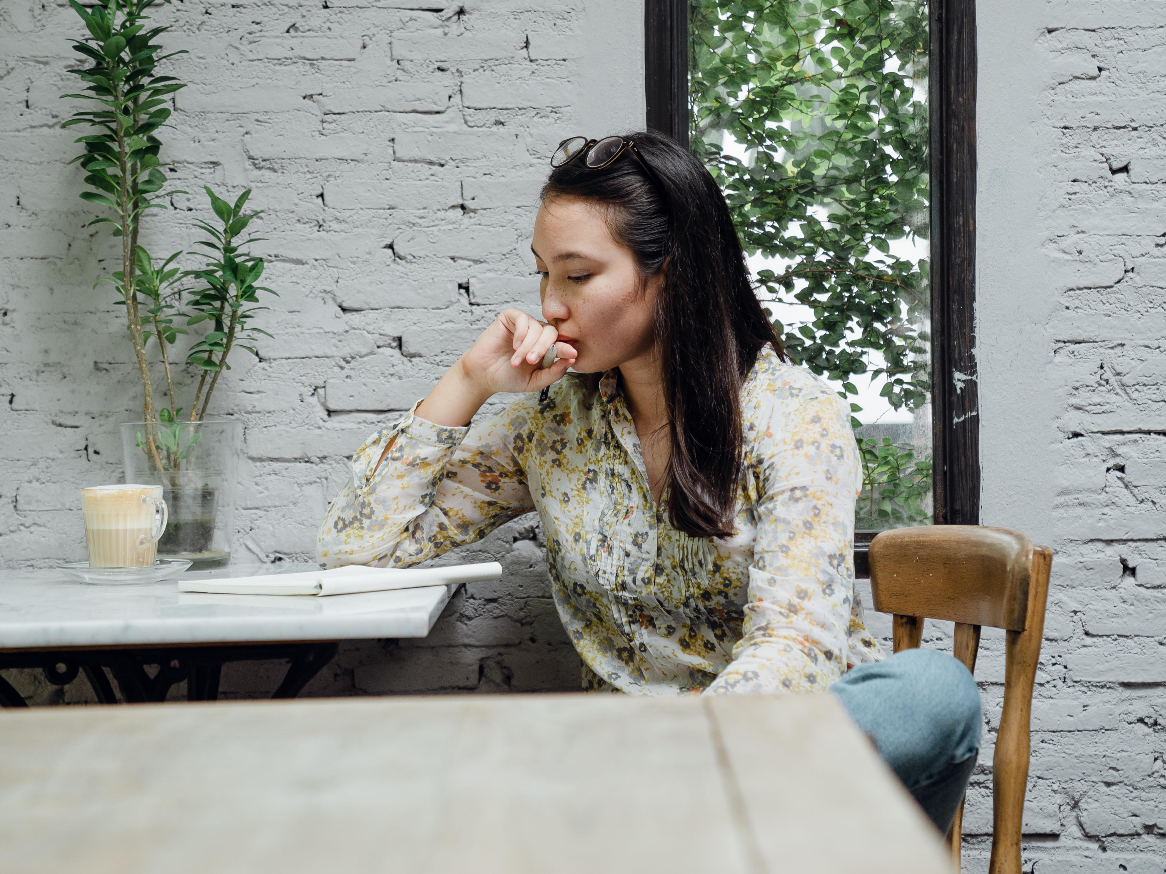focused-young-asian-woman-thinking-about-project-in-4350177