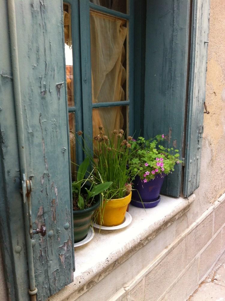 Un-shuttered windows and flowerpots