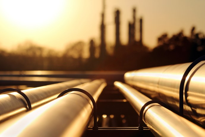 Gas pipes leading to city horizon at sunset - Energy supply capability