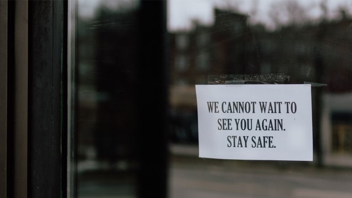 "Closed business door with note saying""We cannot wait to see you again stay safe"" - Business insurance is essential during COVID-19"