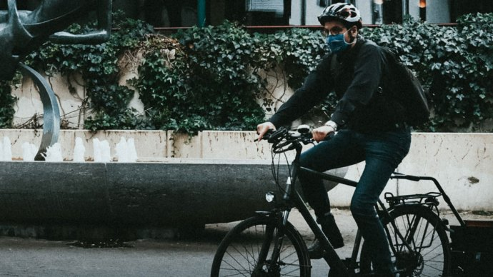 Man on bike with face mask - Lockdown makes climate change targets more achievable