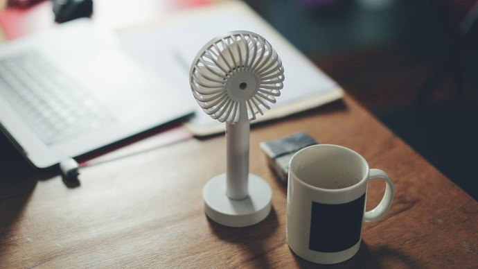 Fan and mug on desk - 5 Reasons Your Business Needs Air Conditioning