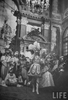 """Couturier Jacques Fath's Sun King costume was so tightly fitted and heavy with embroidery it required him to remain standing in his gondola. Accompanied by his wife Genevieve dressed as """"Queen of the Night""""."""