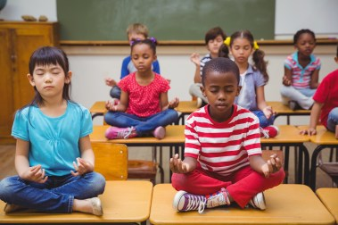 Pupils meditating in lotus position on desk in classroom at the elementary school