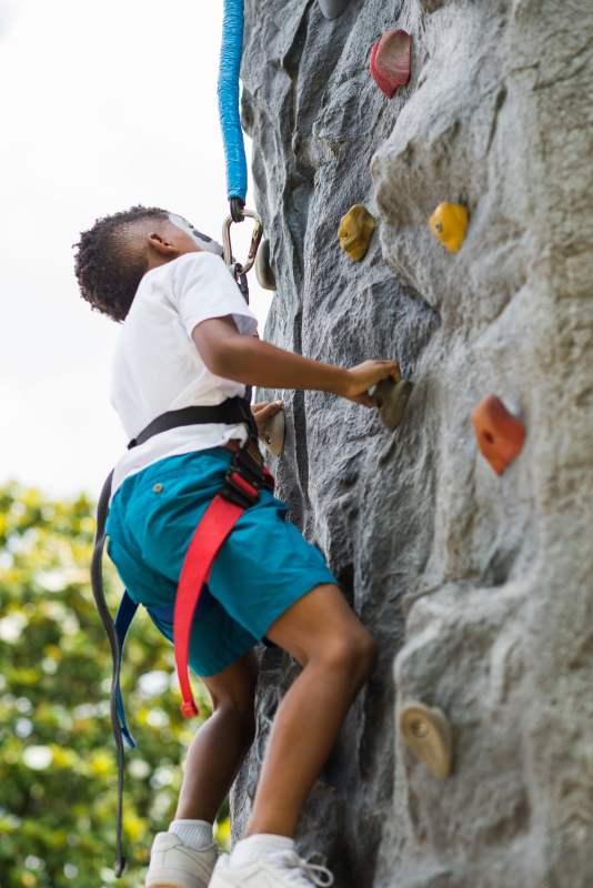 Kid on rock climbing wall at Vulcan Park's Birthday Bash