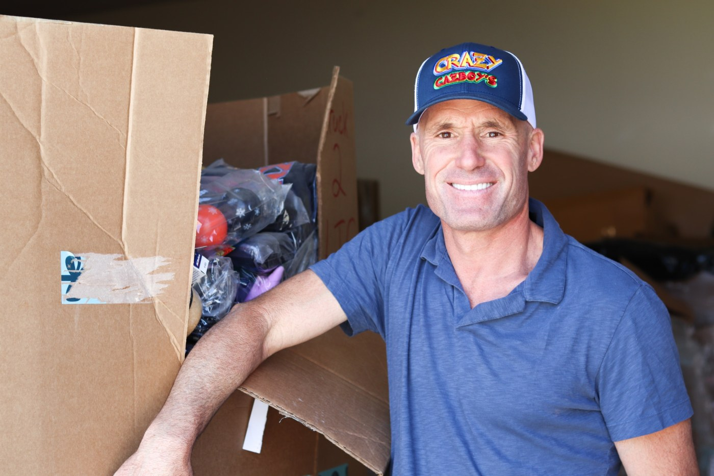 Crazy Cazboy a.k.a John Cassimus stands in front of one of the many large boxes of liquidated goods in the Crazy Cazboy warehouse. Cassimus will open the discount store Friday, May 10th in Homewood. (Photo by Christine Hull for Bham Now)