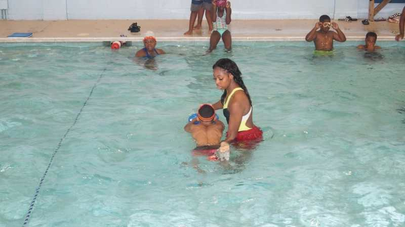 Woman teaching child how to swim