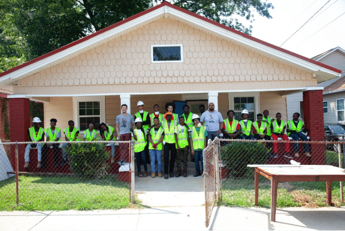 Build UP participants in front of a home in Ensley.