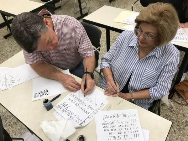 Man and woman practice calligraphy at Samford Academy of the Arts