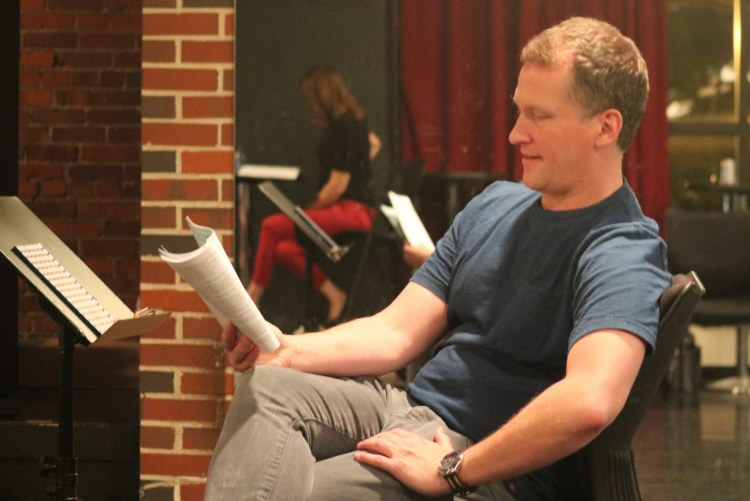 Director following along as the cast rehearses