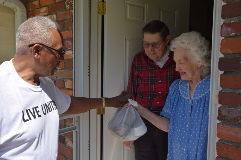 A man greets an elderly couple at their door with a warm meal