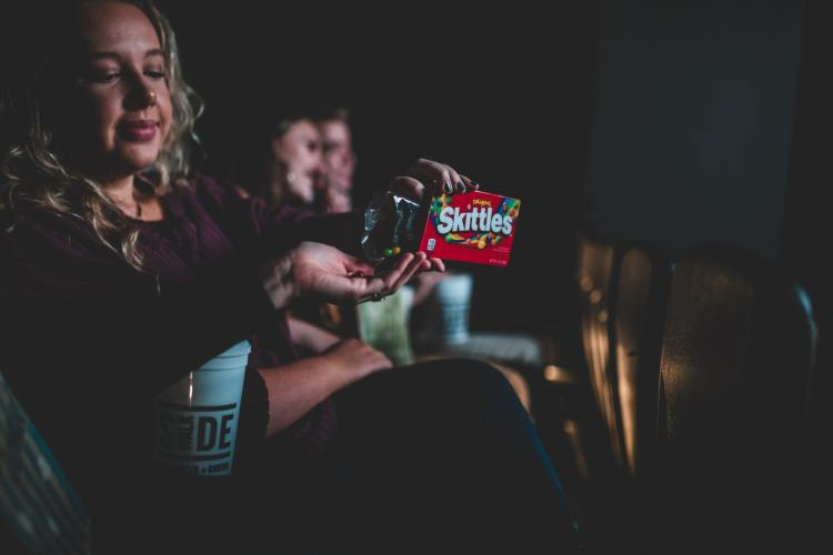 Someone shares Skittles with another person in the theater.