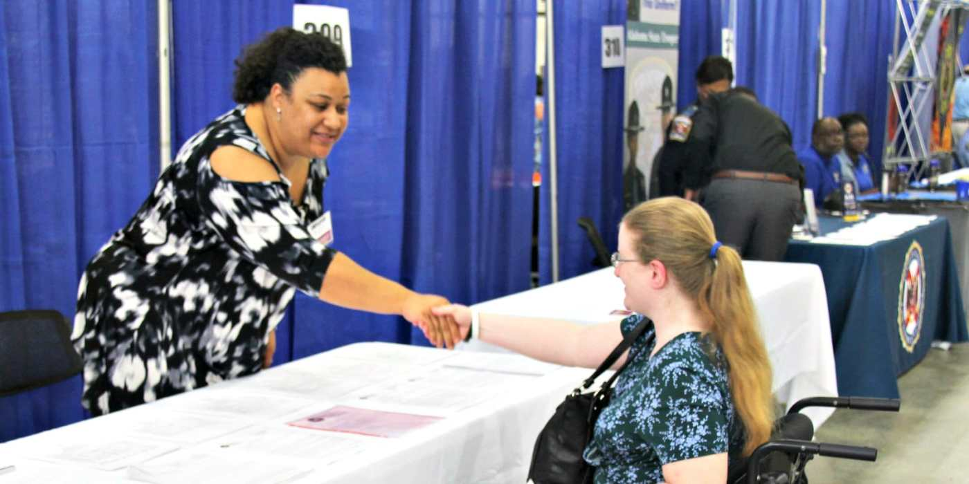 Alabama Department of Rehabilitation Services working with a participant in a wheelchair at a job fair