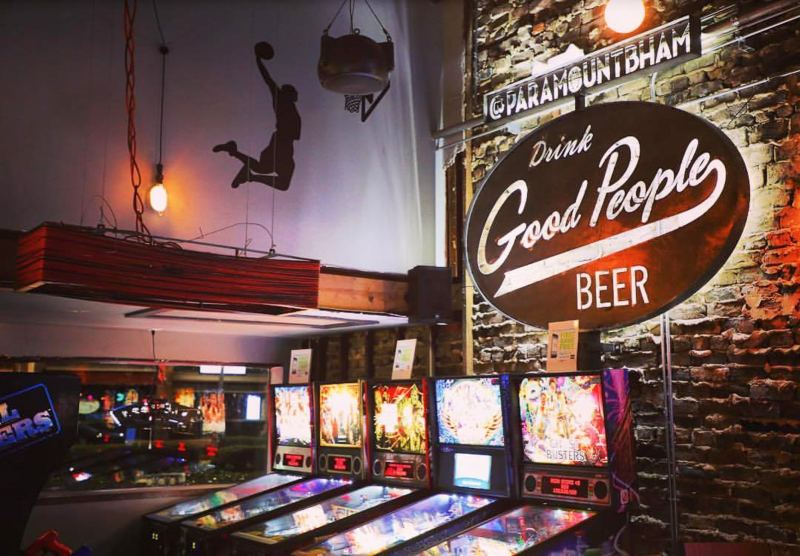 Pinball machines lined up in a bar against a brick wall