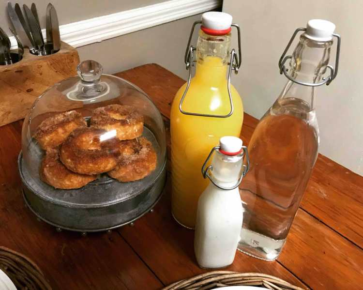 Donuts and orange juice on a counter.
