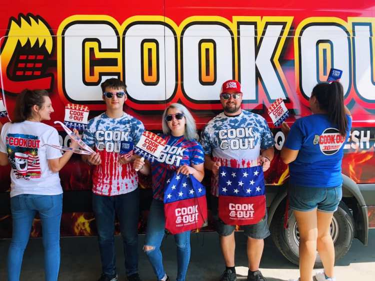 Employees pose with Cook Out merchandise