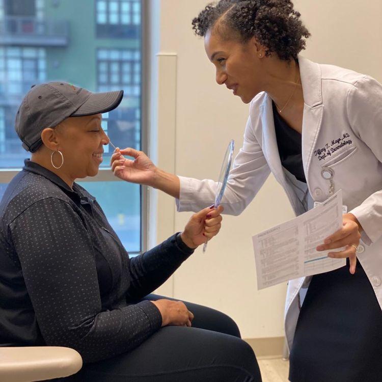 A UAB medical professional assists a patient.