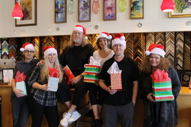 The staff of Four Corners Gallery poses together with holiday gift bags while wearing Santa hats.